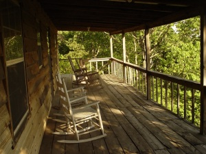 Rocking chairs welcome guests to the front porch of a rustic log cabin